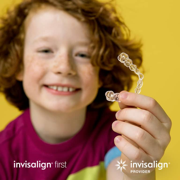 Invisalign first kid holding invisalign